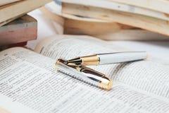 Open woordenboek met pen Stock Foto