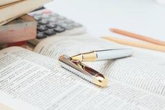 Open woordenboek met pen Stock Afbeelding