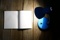 Open writing-book and the fixture. On a wooden background Royalty Free Stock Image