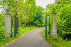 Open wrought iron gate between two stone pillars. Driveway of an estate between an opened wrought iron gate between two stone pillars Stock Images