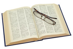 Open yellowed old book with glasses Royalty Free Stock Photo