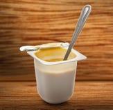 Open yogurt in pot with metal spoon Stock Images
