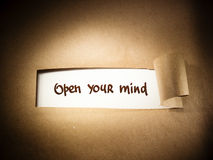 Open Your Mind appearing behind torn paper Royalty Free Stock Photo