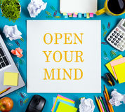Open your mind. Office table desk with supplies, white blank note pad, cup, pen, pc, crumpled paper, flower on blue Royalty Free Stock Image