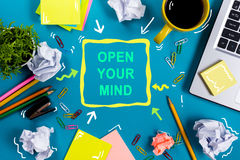 Open your mind. Office table desk with supplies, white blank note pad, cup, pen, pc, crumpled paper, flower on blue Stock Images