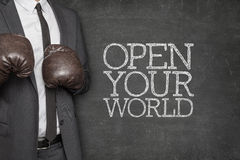 Open your world on blackboard with businessman on. Open your world on blackboard with businessman wearing boxing gloves royalty free stock photography