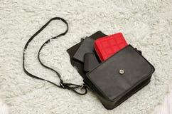 Open zwarte zak met dingen, mobiele telefoon, rode beurs Grijs bont op achtergrond Het concept van de manier Royalty-vrije Stock Foto's
