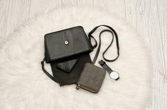 Open zwarte zak met een morserij uit haar telefoon, een grijze beurs en een horloge Het witte bont op achtergrond, hoogste mening Royalty-vrije Stock Afbeeldingen
