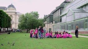 Openair lesson for elementary school children, Botanical garden near greenhouse. Paris, France- June 7, 2018: Jardin de Plantes - main botanical garden. The stock video footage