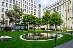Openbaar park tussen moderne bureaugebouwen, toekomst van het werk, het coworking, gedeeld werkplaatsconcept, zonnige dag royalty-vrije stock foto's