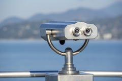 Openbare binoculair op overzeese kust, sluit omhoog Het muntstuk stelde binoculaire kijker op vage achtergrond van zonsondergang  stock foto's