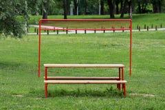 Openbare parklijst en banken voor netto het volleyball van het metaalkader omringd met ongesneden gras en bomen in lokaal park stock foto's
