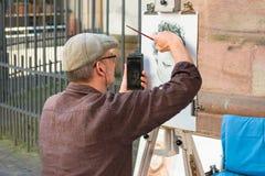Openbare schilder of straatkunstenaar die een portret schetsen in openlucht en een smartphone gebruiken Heidelberg, Duitsland - S Royalty-vrije Stock Afbeelding