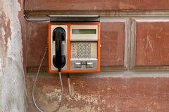 Openbare telefoon op grungemuur Stock Foto's