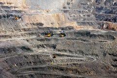 Opencast mine. Quarry extracting iron ore with heavy trucks, excavators, diggers and locomotives Stock Photos