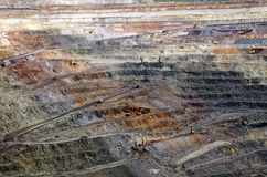 Opencast mine. Close up of quarry extracting iron ore with heavy trucks, excavators, diggers and locomotives Royalty Free Stock Photography
