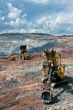 Opencast mine. A picture of a big yellow mining truck,excavator and bulldozer at worksite Stock Image