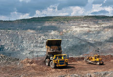 Opencast mine. A picture of a big yellow mining truck and bulldozer at worksite Stock Image