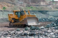 Opencast mine. A picture of a big yellow bulldozer at work site Stock Photos
