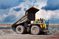Opencast mine. A picture of a big yellow dumping mining truck Stock Image