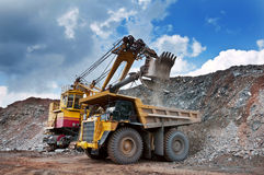 Opencast mine. Excavator loading iron ore into the heavy dump truck on the iron ore opencast mining Stock Images