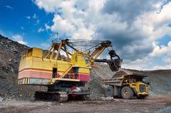 Opencast mine. Excavator loading iron ore into the heavy dump truck on the iron ore opencast mining Royalty Free Stock Photo