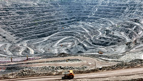Opencast mine. Quarry extracting iron ore with heavy trucks, excavators, diggers and locomotives Royalty Free Stock Image