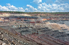 Opencast mine. Close up of quarry extracting iron ore with heavy trucks, excavators, diggers and locomotives Stock Photography