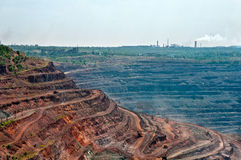 Opencast mine. Close up of quarry extracting iron ore with heavy trucks, excavators, diggers and locomotives Stock Images