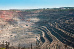 Opencast mine. Close up of quarry extracting iron ore with heavy trucks, excavators, diggers and locomotives Royalty Free Stock Image