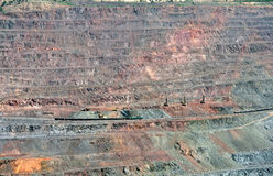 Opencast mine. Close up of quarry extracting iron ore with heavy trucks, excavators, diggers and locomotives Royalty Free Stock Photo