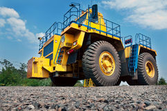 Opencast mine. A picture of a big yellow mining truck at worksite on blue sky with white clouds background Stock Images