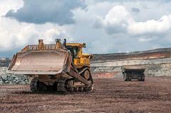 Opencast mine. Big yellow excavator and mining truck at worksite Stock Images