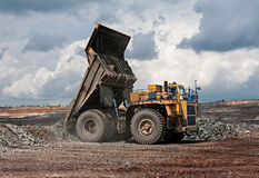 Opencast mine. Big yellow mining truck unload iron ore Royalty Free Stock Images