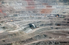 Opencast mine. Close up of quarry extracting iron ore with heavy trucks, excavators, diggers and locomotives Stock Photo