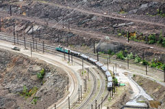 Opencast mine. Close up of quarry extracting iron ore and wagons Royalty Free Stock Photo