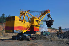 Opencast mine. Excavator loading iron ore into goods wagon on the iron ore opencast mine Royalty Free Stock Images