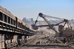 Opencast mine. Excavator loading iron ore into goods wagon on the iron ore opencast mine Stock Photography