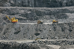 Opencast mine. Excavator loading iron ore into the heavy dump truck on the iron ore opencast mine Royalty Free Stock Photography