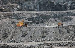Opencast mine. Excavator loading iron ore into the heavy dump truck on the iron ore opencast mine Royalty Free Stock Image