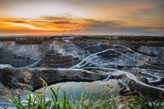 Opencast mining quarry with beautiful sunlight and cloudy sky Aerial view industrial royalty free stock photo