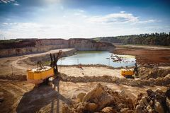 Opencast sand mining quarry with excavator and other machinery at work, industrial production of pit, gravel, minerals and ore. Toned Royalty Free Stock Photography
