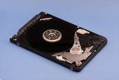 Opened拆卸了硬盘从计算机,与镜子作用的hdd 在蓝色背景 免版税图库摄影