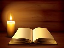 Opened ancient book and candle on dark Royalty Free Stock Photo