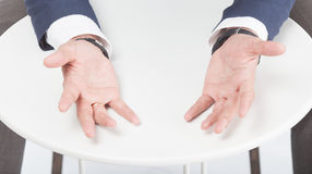 Opened arms. Mens hands in suit showing openg arms on the white table Stock Photo