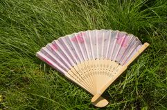 Opened a bamboo fan lying on the grass, copy space royalty free stock image