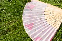 Opened a bamboo fan lying on the grass, copy space royalty free stock photo