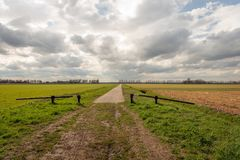 Opened barrier at the beginning of a long straight road Royalty Free Stock Image