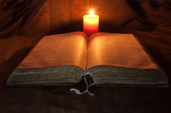 Opened Bible and Candle. Close-up of an old opened Bible, and candle Royalty Free Stock Photos