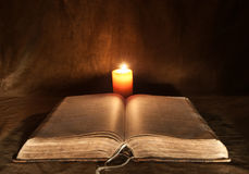 Opened Bible and Candle. Close-up of an old opened Bible, and candle stock photos